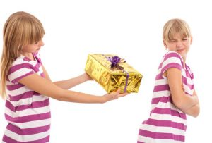 Young female trying to give a gift to her sister who is rejecting it. Studio isolated shot.