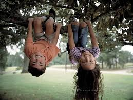 kids hanging upside down on playground
